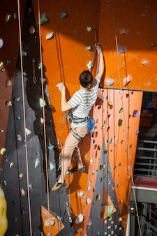 Climber young man climbing on practical wall indoor