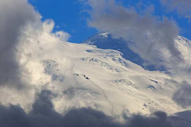 Climbers trail on the eastern top of mount elbrus, the slope with snow is visible through the clouds. mountain range in the north caucasus in russia.
