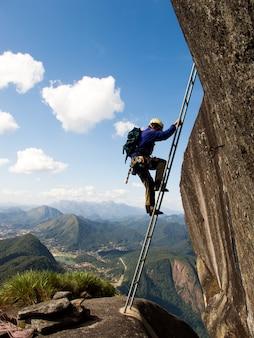 Climbing a ladder to dedo de deus summit