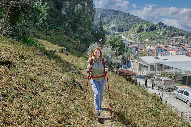 Восхождение на гору с палками и рюкзаком, молодая рыжеволосая европейка гуляет по окраинам города фетхие в турции.