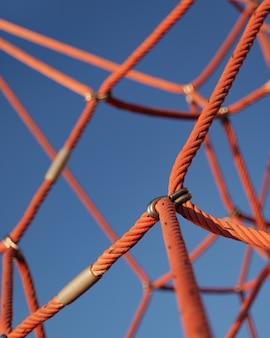Альпинистская веревочная сеть с фоном голубого неба. крупный план части спортивно-игрового комплекса.