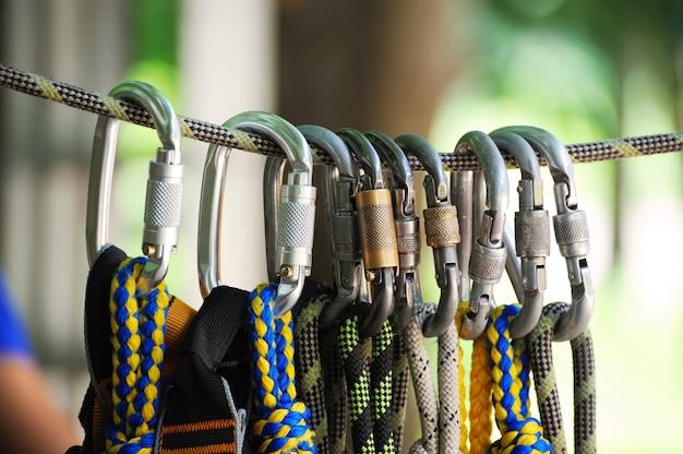Восхождение на спортивный образ карабина на веревке в лесу