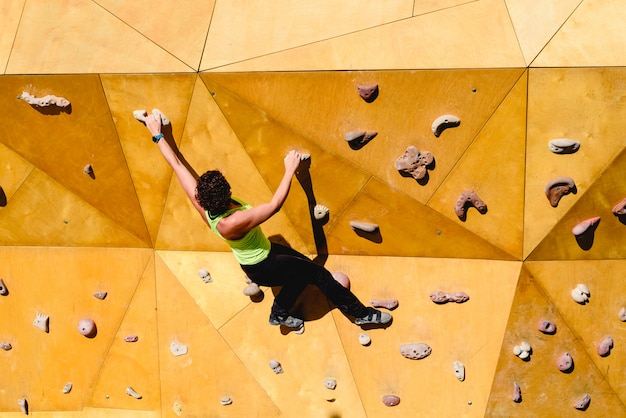 Climbing wall with strong woman in good shape doing exercise outdoors