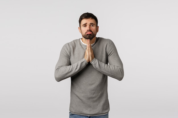 Clingy and cute bearded guy want something badly, make promise, pouting looking angelic tender expression asking help or mercy, hopefully press hands together pray, begging