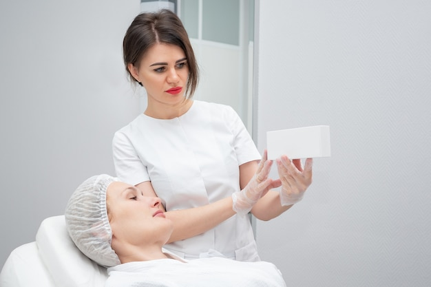 Специалист клиники показывает клиентке новое современное лекарство от преждевременного старения в косметологическом кабинете