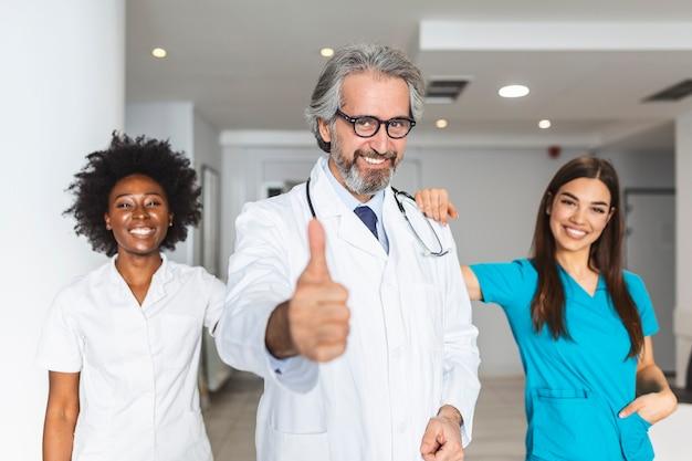 클리닉, 직업, 건강 관리 및 의학 개념 병원 복도에서 위생병 또는 의사의 행복 그룹입니다.