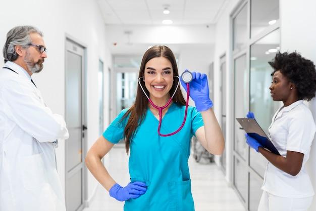 クリニック、職業、人々、ヘルスケア、医学の概念は、病院の廊下にいる医者や医師の幸せなグループです。