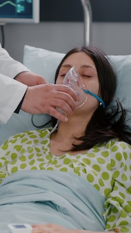 병원 병동 호흡 응급 상황에서 호흡 상태를 분석하는 산소 마스크를 착용 한 환자를 모니터링하는 임상 팀
