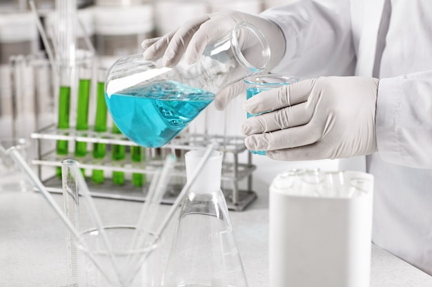 Clinical worker dressed in white gown and gloves holding glass beakers with blue liquid