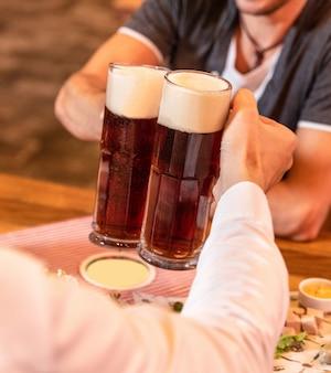 素晴らしく暗い、黒いビールジョッキのクローズアップ、テーブルのスナック