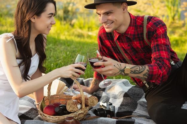 チリンと鳴るメガネ。夏の日に公園で一緒に週末を楽しんでいる白人の若い、幸せなカップル