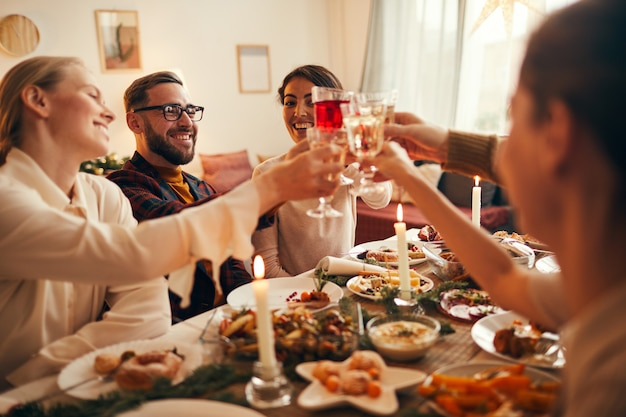 Clinking glasses at dinner party