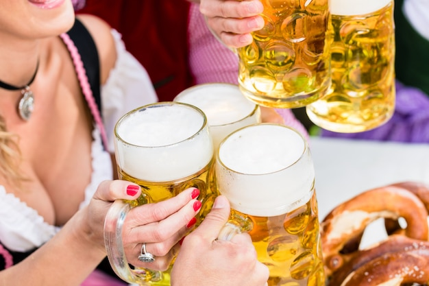 Clinking glasses with beer in bavarian pub