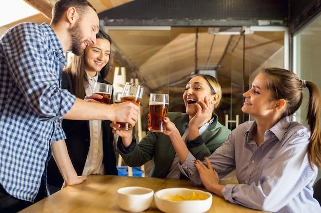 Звон. счастливые коллеги празднуют корпоративное мероприятие после напряженного рабочего дня. выглядят довольными, приветливыми, веселыми. пью пиво. концепция офисной культуры, совместной работы, дружбы, праздников, выходных.