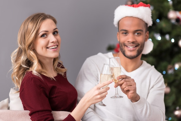 Звон бокалов. веселая счастливая позитивная пара держит бокалы и пьет шампанское во время празднования нового года