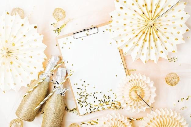 황금 장식으로 클립보드와 샴페인입니다. 평평한 평지, 최고 전망의 세련된 휴가 개념.