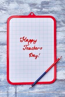 クリップボードとダブルペンシル。教師の日おめでとうございます。