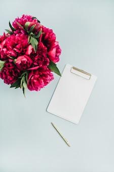 파스텔 블루 표면에 클립 보드와 분홍색 모란 꽃 꽃다발