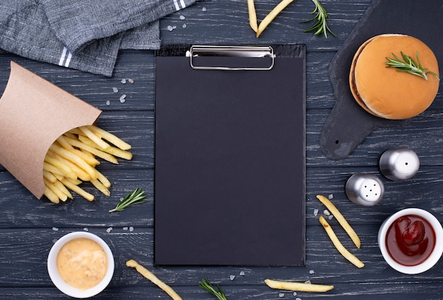 Clipboard beside delicious hamburger with fries