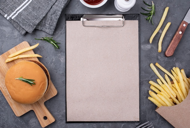 Clipboard beside hamburger and fries