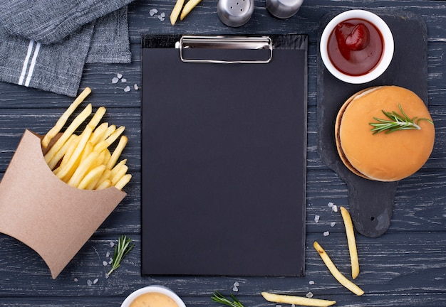 Clipboard beside hamburger with fries