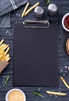 Clipboard beside tasty hamburger with fries