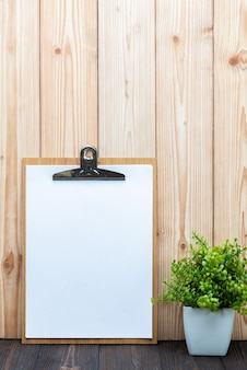 Clipboard blank white paper sheet with little tree on wood