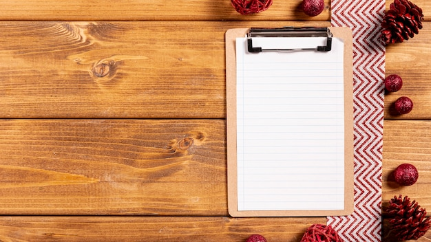 Clipboard and christmas decorations on wooden table