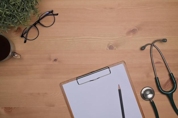 Доска сзажимом для бумаги, кофейная чашка и стетоскоп на деревянном столе.
