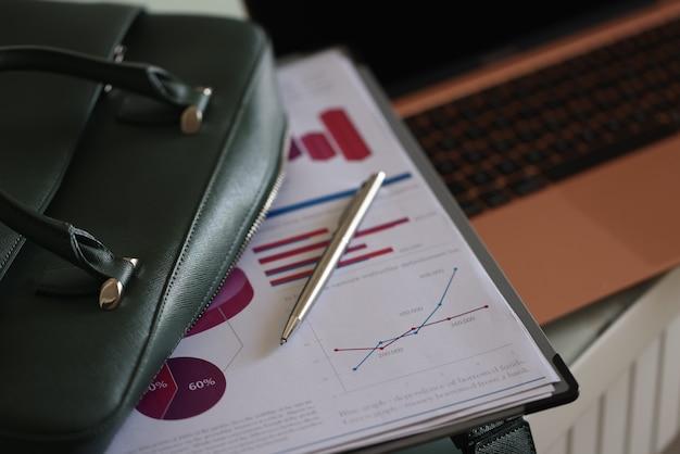 Буфер обмена документы и шариковая ручка, лежащая на открытой зеленой сумке для ноутбука крупным планом