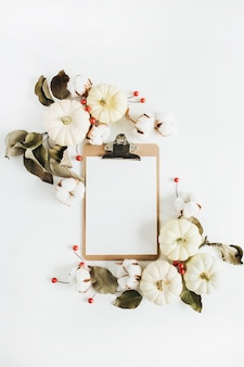 Clipboard and frame of white pumpkins, red berries and eucalyptus branches on white background. flat lay, top view