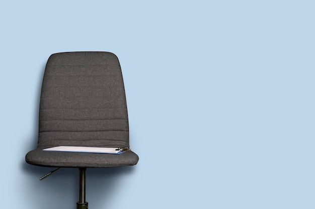 Clipboard lies on a gray office chair on a blue.