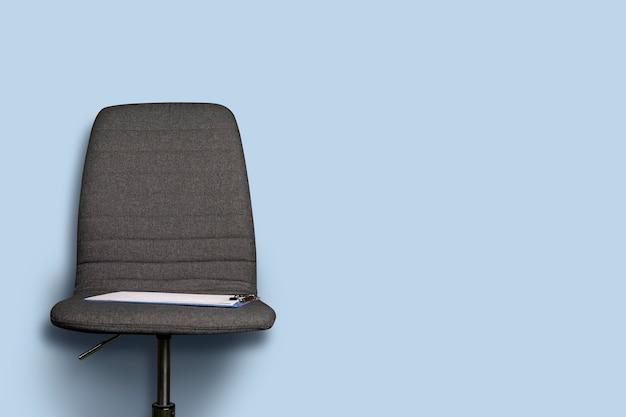 Буфер обмена лежит на сером офисном стуле на синем.