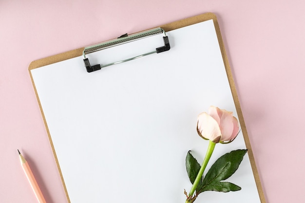 Clipboard  on light pink table with pink rose. copy space.