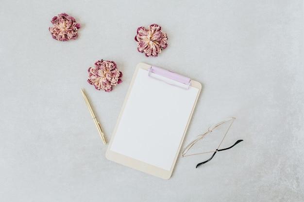 クリップボード。乾いた牡丹、メガネ、ペンを備えた最小限のホームオフィスデスク Premium写真