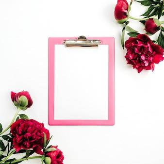 白い表面にピンクの牡丹の花のフレームでクリップボードのモックアップ