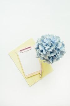 Макет буфера обмена с бумажной заготовкой и букетом цветов синей гортензии на белой поверхности