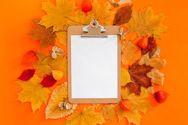 Макет буфера обмена и сухие листья на смелом оранжевом цветном фоне