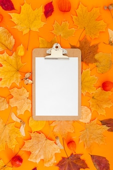 Clipboard mockup and dry leaves on orange background