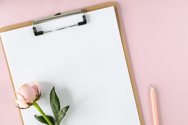 ピンクのバラと淡いピンクの背景にクリップボードのモックアップ。スペースをコピーします。