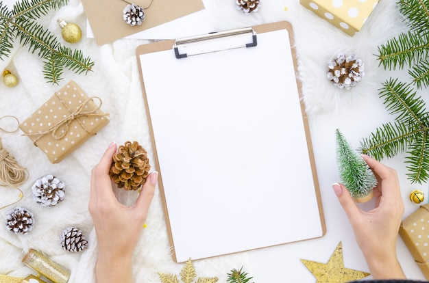 Clipboard mockup with christmas decor. woman holding christmas tree