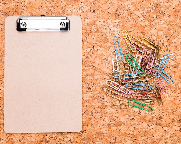 Clipboard and multicolored paper clips on cork background