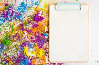 Clipboard near blurs and heaps of different bright dry colors