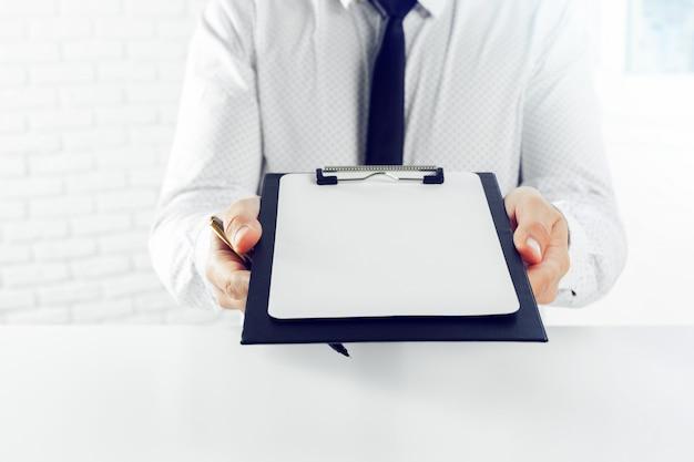 白いテーブルの上のクリップボード。閉じる