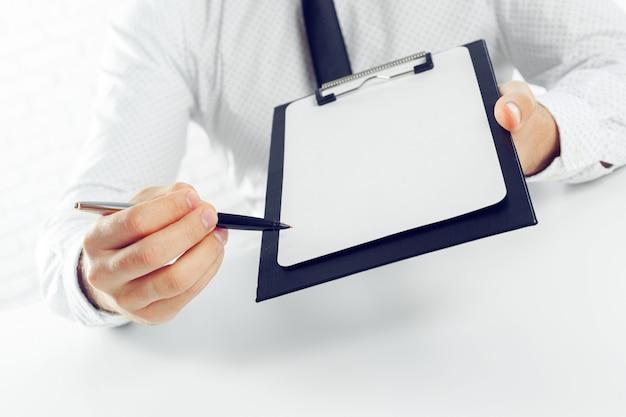 Доска сзажимом для бумаги на белом столе. закрыть