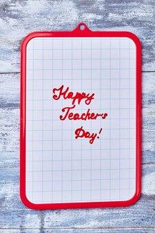Буфер обмена на деревянных фоне. простое поздравление с днем учителя.