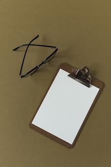 Блокнот для буфера обмена с чистым листом бумаги и очками на оливковой поверхности