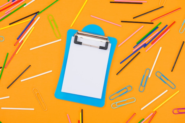 Clipboard, paper clips on yellow table .