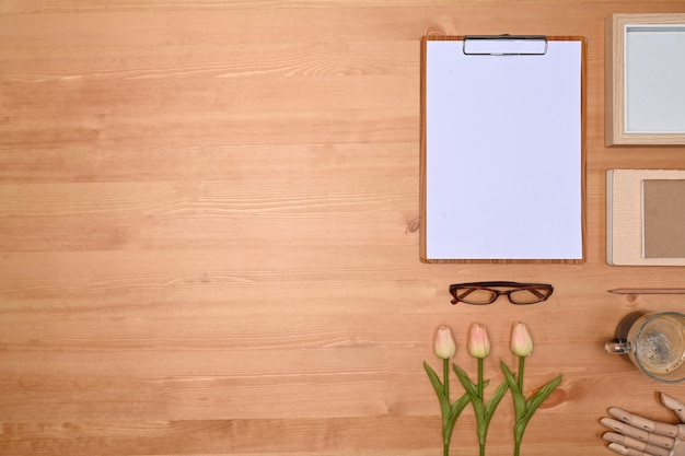 Clipboard, picture frame, flowers and coffee cup on wooden background.