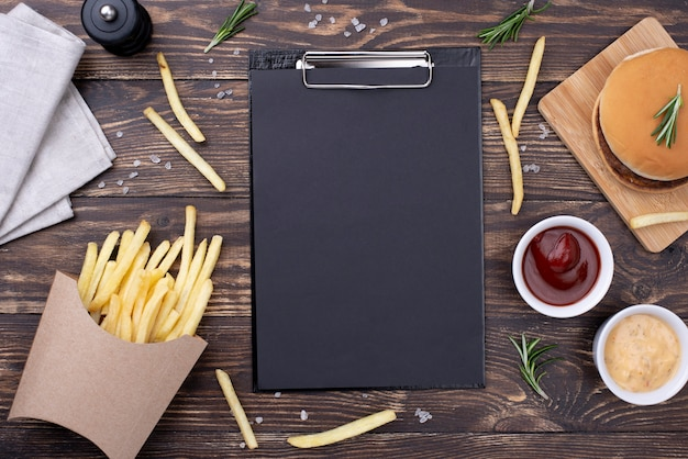 Clipboard on table with hamburger and fries